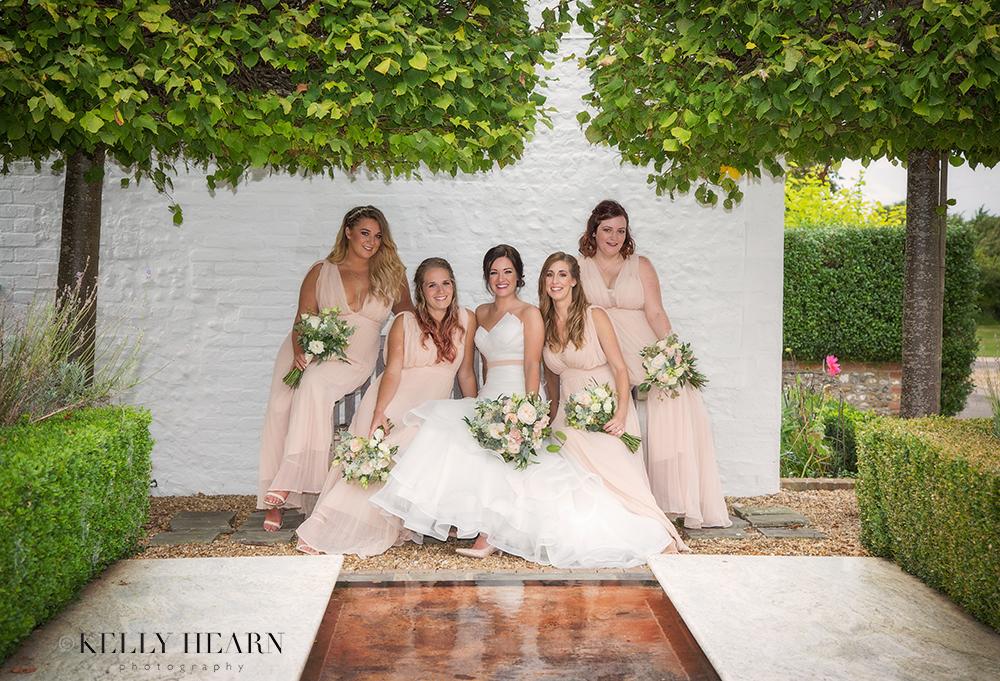 HAR_bride-bridesmaids-on-bench-garden.jpg#asset:1815